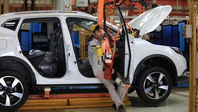 In this July 15, 2016, photo, a worker sits in a car on the assembly line at a Dongfeng Nissan joint venture manufacturing plant in Dalian in northeastern China's Liaoning province.