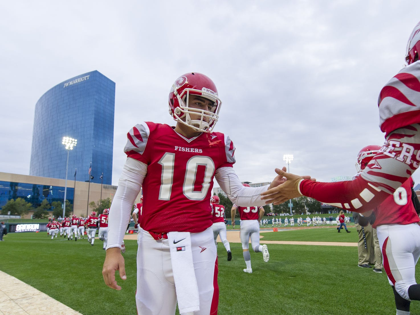 Fishers High School senior Zach Eaton (10) fires up his teammates as the head onto the field to warmup during pre-game activities of an IHSAA Varsity football game being held at Victory Field in Indianapolis, Friday, October 2, 2015.