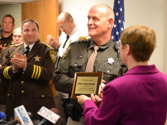 Brown County Sheriff's Department Deputy Greg Gleason, center, is awarded the Truttmann Award on Dec. 2, 2014, for making the most drunken driving arrests. Presenting the award is Wanda Truttmann Sieber, daughter of the Brown County sergeant, Jim Truttman, for whom the award is named.