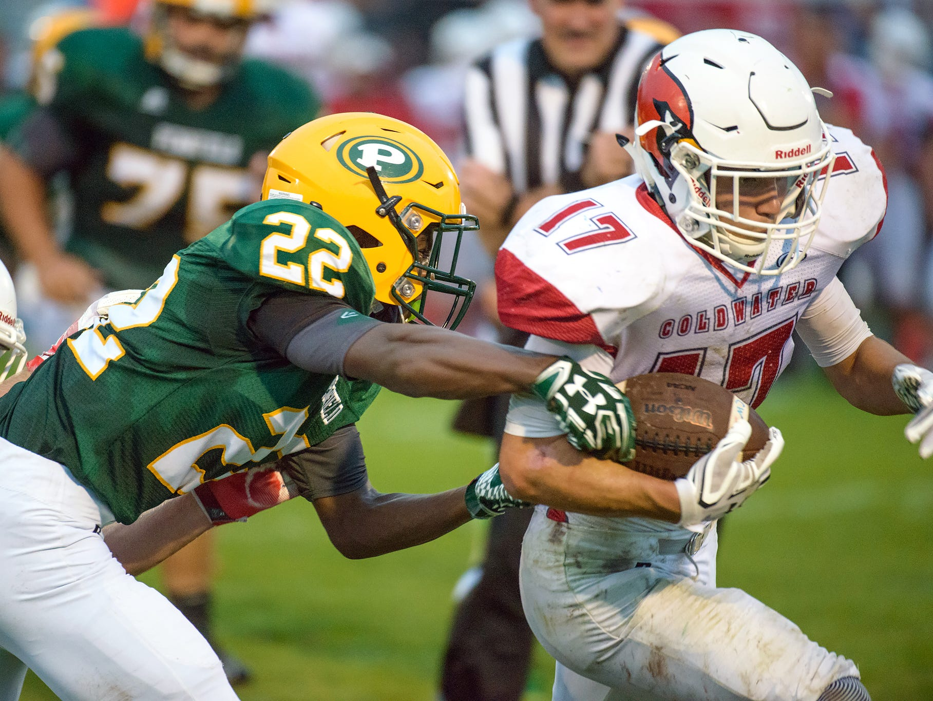 Pennfield's Kaleb Little (22) works to force a fumble on Cardinal running back Joey Severn (17) late in the second quarter of play Friday night.