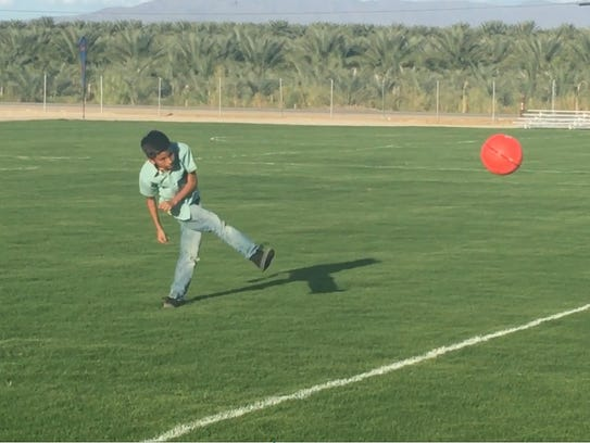 A child christens the first Oasis public soccer field,
