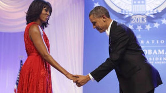 President Barack Obama bows as he and first lady Michelle Obama, wearing a ruby-colored chiffon and velvet Jason Wu gown, get ready to dance at the Inaugural Ball Jan. 21, 2013.