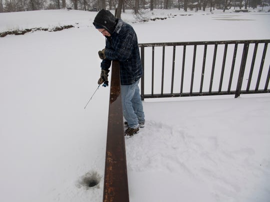 Isaac Morris of Evansville braves the falling snow and low temperatures to get some fishing in at Garvin Park Monday morning. Morris used a long pipe to bust a hole in the thin, snow-covered ice and a container of bee moths to coax the crappie and bluegill to bite. The avid fisherman also catches trout and bass at the popular fishing spot, but didn't catch any of those this day.