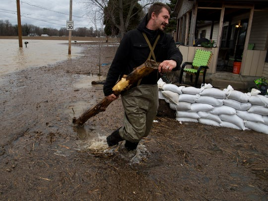 Jason Weese removes a log from his West Side Evansville front yard on Red Bank Road Thursday afternoon. Weese has been battling the Ohio River for the past week and has so far been able to keep the water out of his house.