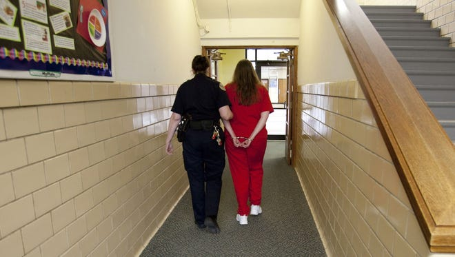A female prisoner is returned to solitary confinement.