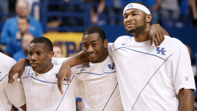 Kentucky players, from left to right, Eric Bledsoe, John Wall and DeMarcus Cousins watch senior day activities prior to their game against Florida in Lexington, Ky., Sunday, March 7, 2010.
