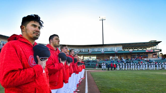 Peoria Chiefs players line up for the playing of the National Anthem during the 2019 home opener at Dozer Park.