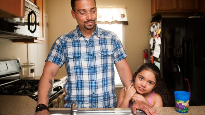 "Tatyana ""Tuffy"" Rivera, 7, holds on to her father, Ricardo, in the kitchen of their home in Camden County, July 31, 2014."