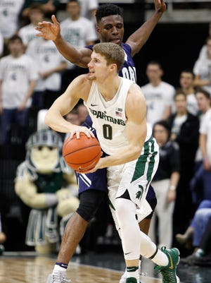 Michigan State guard Kyle Ahrens (0) looks for an open man against Oral Roberts forward Emmanuel Nzekwesi (23) during the first half of MSU's 80-76 win Saturday at Breslin Center.