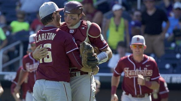 Smoky Mountain alum and Florida State catcher Cal Raleigh hugs a teammate following Monday's win in Omaha, Neb.