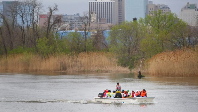 Volunteers participating in the 2011 annual Christina River Cleanup ride in a boat past International Petroleum Corp.'s plant in South Wilmington. The company's distinctive blue tanks can be seen just below the tree line.