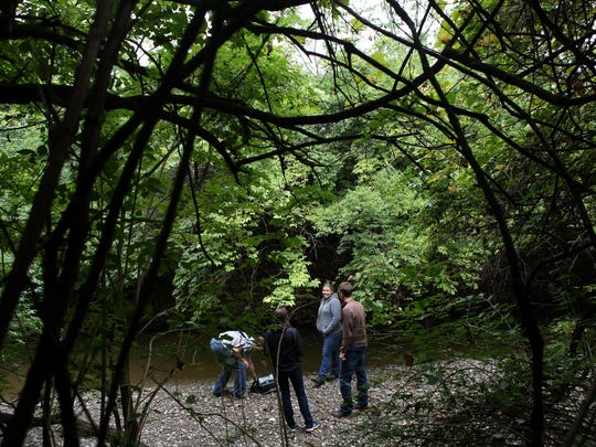A group of citizen scientists collect water from Mill Creek once a month for sampling in Evendale.