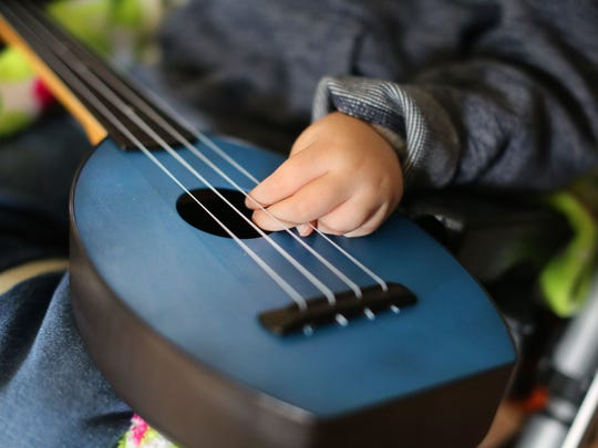 Elias Wendland tries out a small ukulele donated by True Joy Acoustics to Cincinnati Children's Hospital Medical Center's music therapy program.