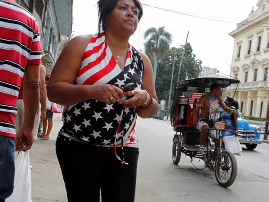 A woman wears a shirt decorated with the U.S. flag as a tricycle taxi, also sporting a U.S. flag, pedals by Saturday in Havana, Cuba.
