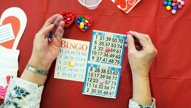 Mary Wolfe of Port Huron places M&Ms on her bingo cards at an annual Senior Valentine's Day Brunch at Port Huron Northern High School. About 50 seniors from the Northport Towers attended the brunch sponsored by the high school's student council.