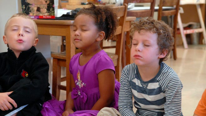 Thomas Theobald, 6, left, Zoe Nicolas, 5, center, and Paul Reno-Webber, 5, right, do a deep breathing exercise during a morning meditation led by kindergarten teacher, Laura Patterson, at Highland Presbyterian Church Nursery and Weekday School.    October 23, 2015