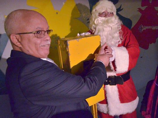 Wayne County Executive Warren Evans helps Santa Claus throw the switch to illuminate Lightfest.