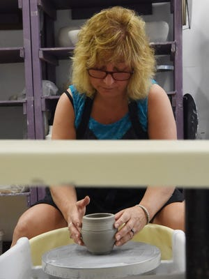 Phyllis Walsh, 57, of Beekman, molds an illuminator out of white clay at Art Centro in the City of Poughkeepsie.