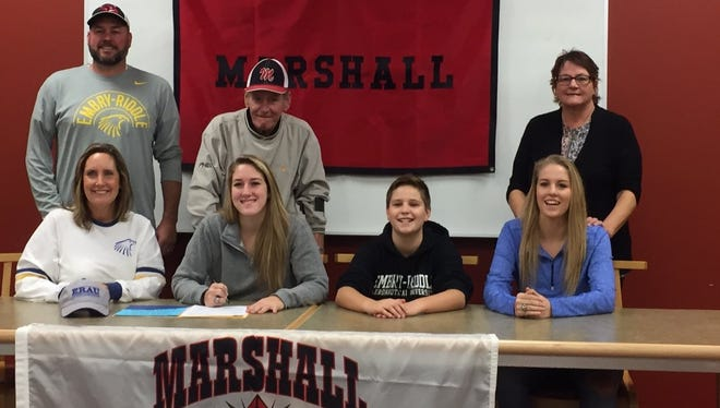 Marshall senior Nikki Tucker (center) is surrounded by family as she signed a National Letter of Intent on Thursday to play basketball at Division II Embry–Riddle Aeronautical University. Standing (L-R) are Brent Tucker, Gene Tucker and Carol Tucker; seated (L-R) are Jackie Tucker, Nikki Tucker, Nate Tucker and Natalie Tucker.