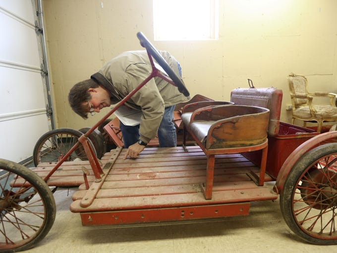 """David Aroh looks at an antique electric car at a state surplus sale at E. P. """"Tom"""" Sawyer State Park of items from historic sites. Dec. 10, 2013."""