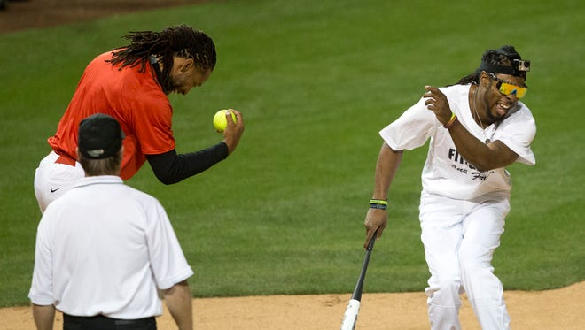 Richard Sherman (right) laughs at catcher Larry Fitzgerald for missing a pop fly during last year's charity softball game.