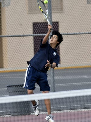 Redwood's John Nguyen serves to Mt. Whitney's Aaron Macagba in the #2 singles match at Mt. Whitney High School on Wednesday, April 25, 2018.