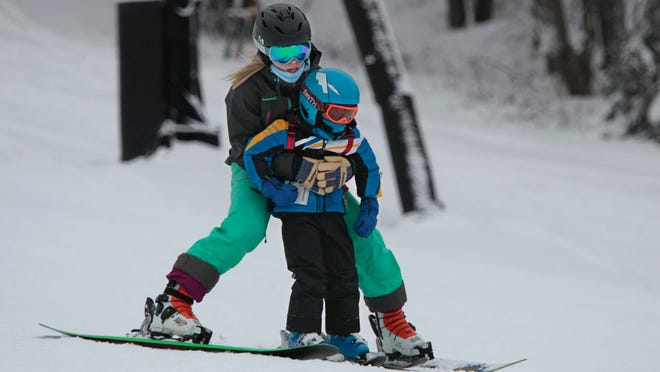 Kimmie Gerrie of Irondequoit lends a helping hand to her brother Colt Fichter, 4, as she teaches him how to ski at Bristol Mountain Friday. Bristol's peak hours of operation, including night time, started Friday.