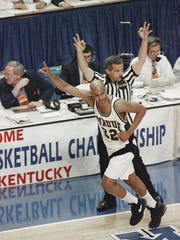 An official raises his arms in the background; Purdue's Cuonzo Martin raises his finger after hitting a three-point score in the first half of their NCAA Regional second-round game against Alabama, on Saturday, March 19, 1994, in Lexington,  Ky.Cuonzo Martin didn't make a 3-point shot for two years, but his success this year is a big reason Purdue made it to the final 16. (AP Photo/Rob Carr)