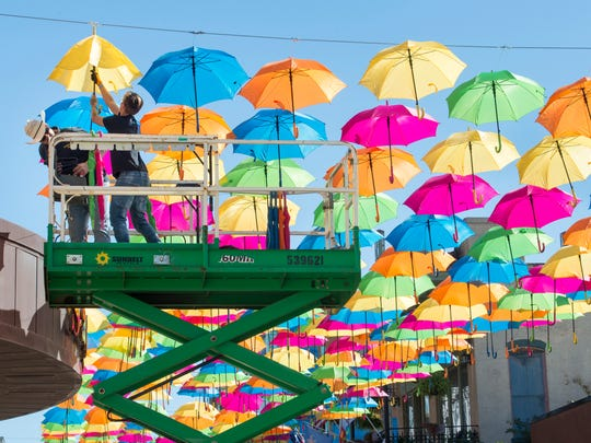Jared Petticrew, of Location FX Inc., left, and artist Inês Martins, of Sextafeira Productions in Águeda, Portugal,  work on installing the Umbrella Sky Project on East Intendencia Street in downtown Pensacola on Monday, October 30, 2017.