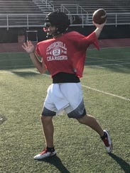 Playing catch during Sunday evening's practice is Livonia