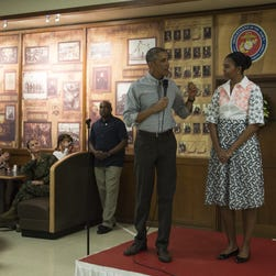 President Barack Obama addresses troops on Christmas Day 2014 at Marine Corps Base Hawaii in Kaneohe, with First Lady Michelle Obama looking on.