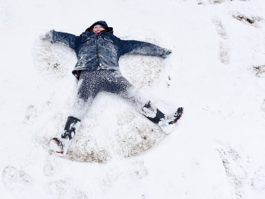 Savannah Stucker makes a snow angel at Betty Virginia
