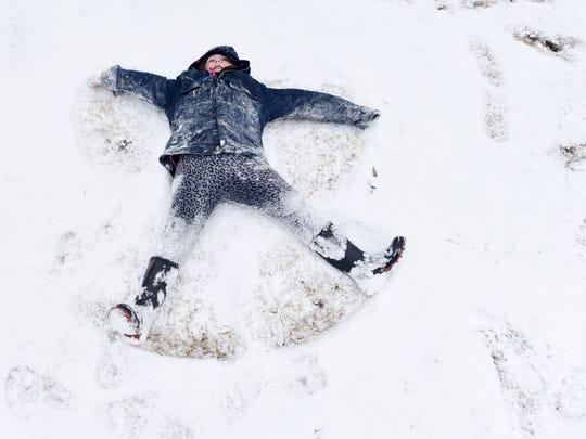 Savannah Stucker makes a snow angel at Betty Virginia