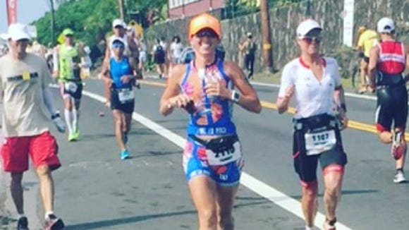 Tammy Nicholson, center, smiles for a photo as she competes in the running leg of the 2015 Ironman World Championships in Kona, Hawaii on Oct. 10, 2015.