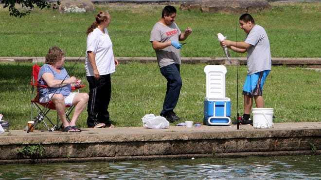 Ann Vincen, left, and Bernadette Plymale look on as Ruben Sanchez helps Juan Reyna, 11, with the catfish he caught, Tuesday, June 2, 2020, while fishing at Carol Ann Cross Park. Today's weather forecast calls for a high of 91 degrees with a chance of scattered thunderstorms.