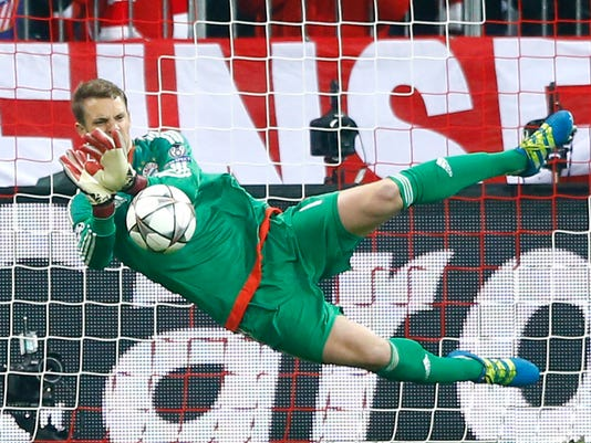 """FILE - In this May 3, 2016 file photo, Bayern goalkeeper Manuel Neuer saves an Atletico's Fernando Torres penalty during the Champions League second leg semifinal soccer match between Bayern Munich and Atletico de Madrid in Munich, Germany. Bayern Munich will have to do without goalkeeper Manuel Neuer for two games because of a foot injury. The Bundesliga leaders say the 31-year-old Germany goalkeeper injured his left foot in training on Wednesday March 29, 2017. Club doctor Markus Walther performed a small operation and the club says it """"went optimally."""" (AP Photo/Matthias Schrader,file)"""