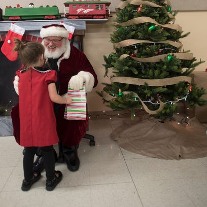 A foster girl gets a present from Santa at a Christmas