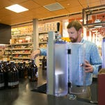 Drew Johnson, beer merchant at a new Liquor Barn location on Shelbyville Road, demonstrates how to use the new growler fillers there. July 1, 2015.