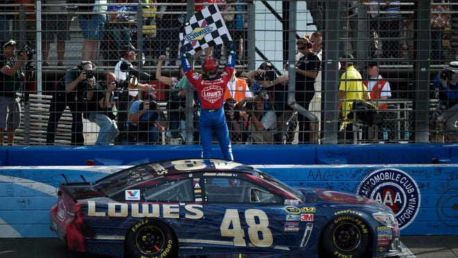 Jimmie Johnson celebrates his win at the Auto Club 400 Sunday.