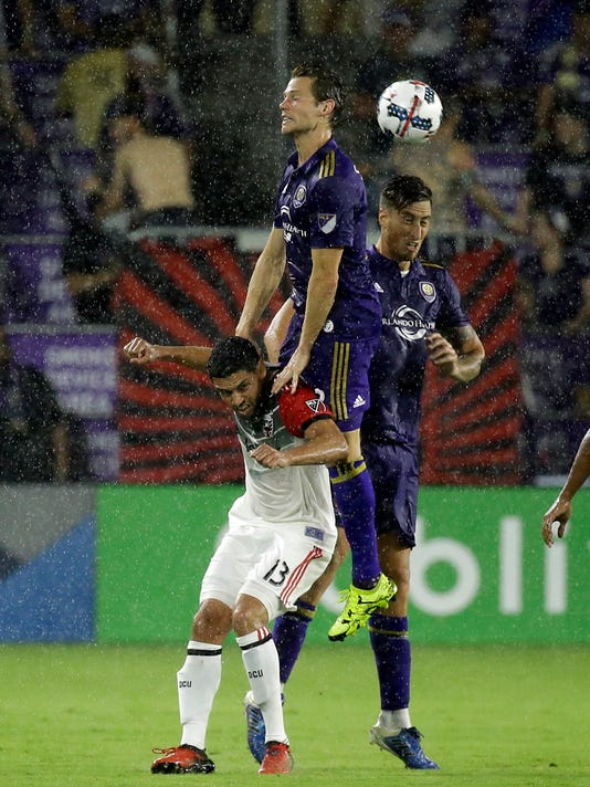 Orlando City's Jonathan Spector, center, and Luis Gil, right, go over the head of D.C. United's Lamar Neagle (13) to gain possession of the ball during the first half of an MLS soccer game, Wednesday, May 31, 2017, in Orlando, Fla. (AP Photo/John Raoux)