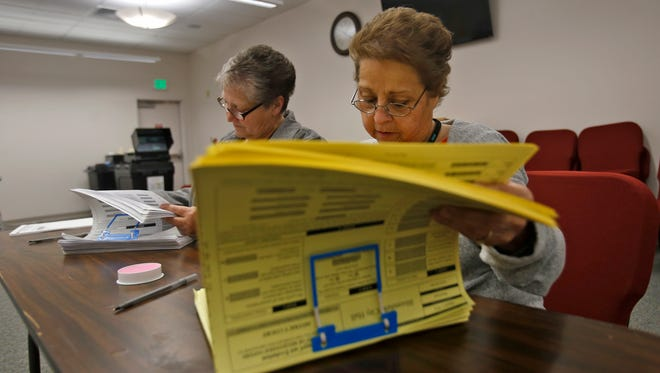 From left, Bloomfield election clerks Rachel Truby and Irene Gallegos look over paperwork for voters on Tuesday at Bloomfield City Hall.