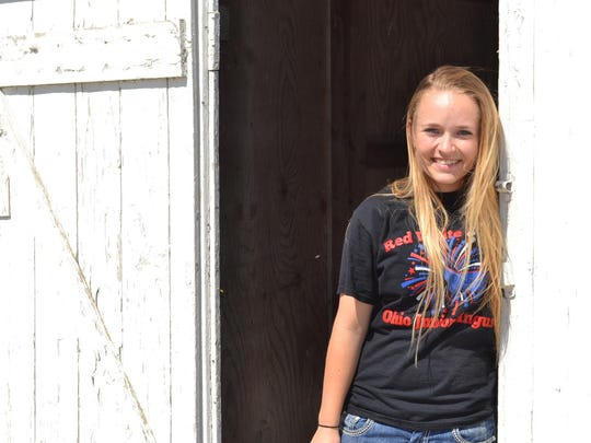 Katie Storey stands outside her barn in rural Clyde. She earned banners this summer at the Ohio State Fair with her heifer, Princess, who won Reserve Champion in the Junior Angus Show, Grand Champion in the Angus Open Show and Best of the Buckeyes.