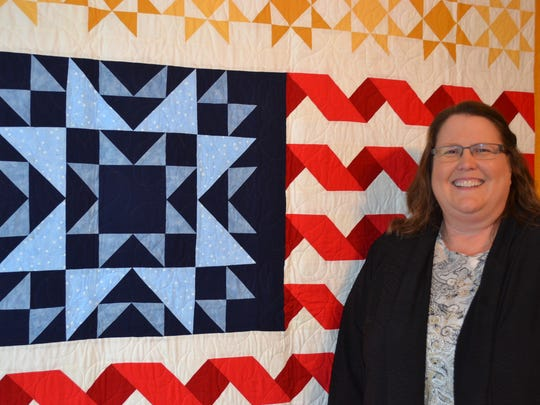 Jill Bothe stands by a flag quilt she made for the Quilts of Valor Foundation, which gives quilts to soldiers touched by war.  Bothe is a former district coordinator and Ohio state coordinator for the foundation.