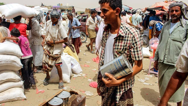 Yemeni civilians receive food aid for displaced people who fled battles in the Red Sea province of Hodeida and are now living in camps under control by the Iranian-backed Huthi rebels in Hajjah on June 24, 2018.