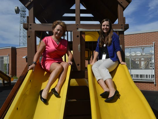 Kathy Hinkfuss, left, and Monica Moe sit at the top of the dual slide on an outdoor playground atop the Green Bay-De Pere YWCA. Hinkfuss has been the YWCA's CEO for three years, and Moe is the longtime organization's development director.
