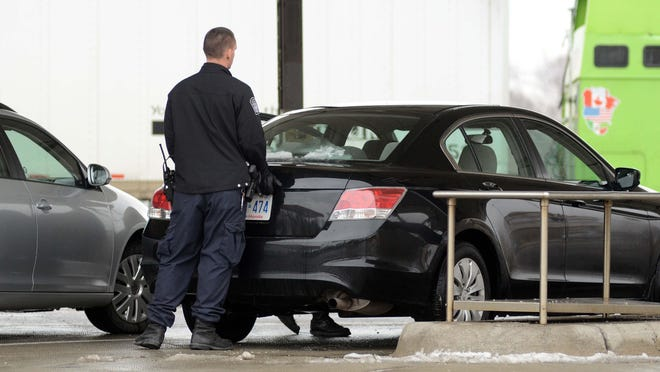 Customs and Border Protection officer searches a car at the Blue Water Bridge.