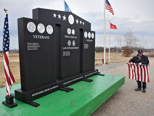 Daryl Steil removes a flag from one side of a scale model of a proposed granite monument Wednesday, March 16, at the Rockville Fire Department. The monument would honor military veterans, police, firefighters and first responders.