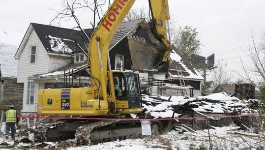 A house on Lyon Street inDetroit is demolished in November 2015.
