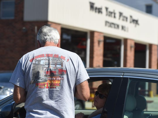 Bruce Klinedinst, a firefighter with the West York Fire Company, takes money to allow a fairgoer to park in a lot on West Market Street. The money raised through the parking lot goes toward purchasing new air tanks for the department.