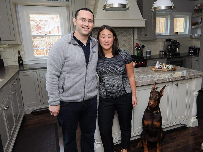Jerry and Kate Suriano stand in their kitchen with their dog, Baron. The kitchen of their three-story Mediterranean-style home is one of their favorite rooms.